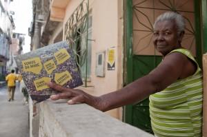Moradora recebe o folder informativo da campanha na Maré Foto: Victor Domingues